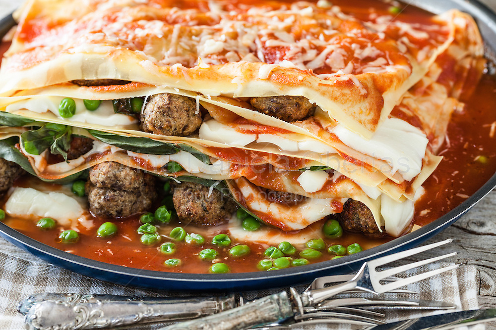 Closeup of lasagna made with meatballs, mozzarella cheese, parmesan, basil, green peas and tomato sauce. Is a traditional neapolitan lasagna except the green peas, not used in the base recipe.