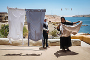 Umm Tarek putting out her husband's laundry to dry, & listening to her daughter who just came back from school, Heisa Island
