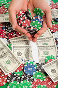Money and Poker Chips on a green felt poke table Hands hold chips