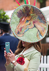 © Licensed to London News Pictures. 19/06/2018. London, UK.  Ines Hernandez wears a horse themed hat while posing for a photograph at day one of Royal Ascot at Ascot racecourse in Berkshire, on June 19, 2018. The 5 day showcase event, which is one of the highlights of the racing calendar, has been held at the famous Berkshire course since 1711 and tradition is a hallmark of the meeting. Top hats and tails remain compulsory in parts of the course. Photo credit: Ben Cawthra/LNP