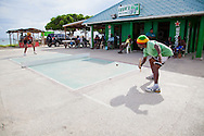 """Originating in Barbados in the 1930s, Road Tennis is played in on the back streets and roads of the country or now in permanent courts, such as the ones in Oistins and Speightstown.  The game is played on a 10x20 foot court and the """"net"""" is an 8 inch by 10 foot piece of wood.  It has the same rules as table tennis (ping pong) and is a 21 point game.  It uses hand hewn rackets made largely from plywood and tennis balls that have had the fur removed.  It is the only endemic sport to Barbados and is wildly popular among the local population.  Pictured here is the road tennis court at Oistins."""