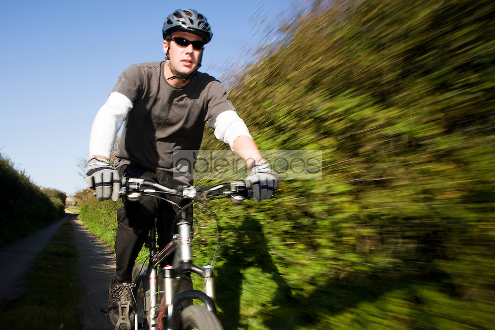 Close up of a man cycling on a country road