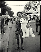 A-J Stahl from Canmore Alberta with his big win of the night a stuffed dog. He had to make 18 baskets in a row with a basketball, calling the experience incredibly hard. Despite living only an hour away, this was his first visit to the Stampede. A little girl of a friend will be getting the dog as a gift. Photo by Todd Korol for The Globe and Mail.