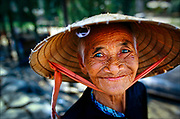 Despite living through years of hardship under the French, the Americans and their Vietnamese allies, and more recently, conflicts with China, an elderly Vietnamese vendor in the coastal city of Hoi An has a ready smile for customers. She wears the nón lá conical hat made of palm leaf and worn by Vietnamese of all ages and both genders.  © Steve Raymer / National Geographic Creative