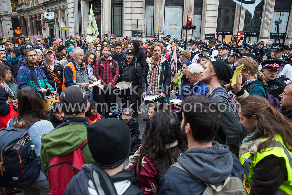London, UK. 14 October, 2019. Climate activists from Scientists for Extinction Rebellion continue to block part of the busy junction at King William Street in front of London Bridge after being pushed back by police officers from the City of London police and Metropolitan Police on the eighth day of International Rebellion protests across London. Today's activities were concentrated around the  City of London's finance district.