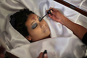 """Marta Reyes applies makeup to the corpse Dina, her murdered daughter, in the """"Lopez"""" funeral home, Guatemala City, Thursday, May 19, 2009. <br /> Guatemala's constant streak of murders ,17-a-day,  provide a steady flow of customers to unregulated  funeral homes, where funeral workers can embalm corpses in the back of auto repair shop or rush to crime scenes to gather information that will allow them to locate, notify and make a sales pitch to the bereaved relatives."""