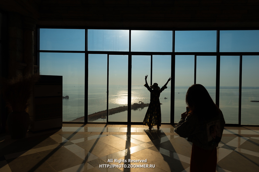 Silhouettes of tourists taking photos in front of windows