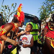 A small boy gets a kiss  from a female dancer. The Notting Hill Carnival has been running since 1966 and is every year attended by up to a million people. The carnival is a mix of amazing dance parades and street parties with a distinct Caribbean feel.