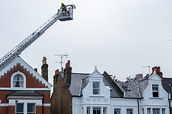 © Licensed to London News Pictures. 07/12/2020. London, UK. An aerial appliance towers over the flat. Ten fire engines and around 70 firefighters responded a flat fire on Montserrat Road in Putney. Firefighters, using breathing apparatus rescued a man via an internal staircase from a second floor flat in a mid-terrace house of three floors. The man was treated for smoke inhalation by London Ambulance Service crews and taken to hospital. Photo credit: Peter Manning/LNP