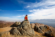 Female hiker enjoys the view from a summit of the colourful Eilat mountains