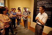 Tour guide in an Ancient Chinese art on show in an exhibition at The National Museum of China flanks the eastern side of Tiananmen Square in Beijing, China. The mission of the museum is to educate about the arts and history of China. It is directed by the Ministry of Culture of the People's Republic of China. The museum was established in 2003 by the merging of the two separate museums that had occupied the same building since 1959. The building was completed in 1959 as one of the Ten Great Buildings celebrating the ten-year anniversary of the founding of the People's Republic of China. After four years of renovation, the museum reopened on March 2011 with 28 new exhibition halls, more than triple the previous exhibition space, and state of the art exhibition and storage facilities. It has a total floor space of nearly 200,000 square meters to display. The renovations were designed by the German firm Gerkan, Marg and Partners.