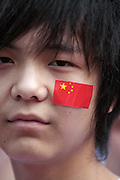 A Chinese teenager wears a Chinese flag sticker on his cheek at the Olympic Torch relay in the southern city of Wuhan.