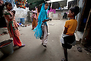 Ruma Akhter (center) walks under washing lines in the slum settlement near her home in Dhaka, Bangladesh. (From the book What I Eat Around the World in 80 Diets.) MODEL RELEASED.