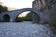 Greece, Epirus, Zagori, Pindus Mountains, a 2 Arched old disused Stone Bridge over a dry riverbed