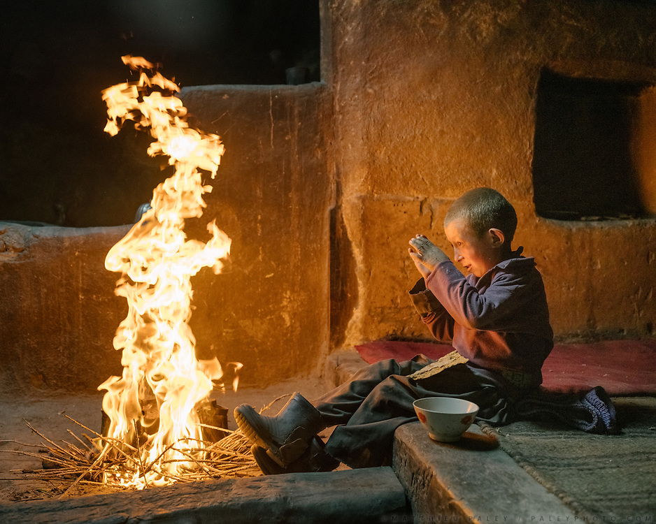 A boy protects himself from the heat of the fire that his mother started in the main room of his house. She will prepare salty milk tea for the boy. People from this region used to be Zoroastrian (Fire and Sun worshippers) before they converted to Islam few hundred years ago. <br /> The traditional life of the Wakhi people, in the Wakhan corridor, amongst the Pamir mountains.