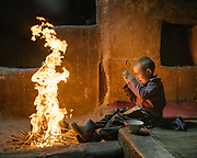 A boy protects himself from the heat of the fire that his mother started in the main room of his house. She will prepare salty milk tea for the boy. People from this region used to be Zoroastrian (Fire and Sun worshippers) before they converted to Islam few hundred years ago. <br />