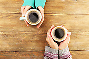 Female hands holding cups of coffee on rustic wooden table background