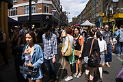Brick Lane street scene on Sunday market day, London, UK. This has become a hang out for hipsters and cool kids and it seems lots of Chinese.