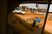 Workers are reflected in a sign at the construction site of a new 50,000-seat sports stadium in Conakry, Guinea on Friday March 6, 2009.  The project, an investment of about USD 50 million, is a gift to Guinea from the Chinese government.(Olivier Asselin for the New York Times).