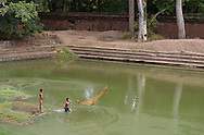A boy fishes in what was once an ancient king's swimming pool in Angkor Wat.