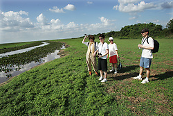 "A group of French and European tourists visit Los Llanos in Venezuela. Los LLanos are the grasslands in western Venezuela famous for the ""llanera"" culture of cowboys and music.  Many working ""Hatos"" , or cattle ranches, dot the landscape of grasslands and river systems, offering tourists a chance to see the beautiful landscape and various wildlife.  Tourists go out on land and water excursions where they get a chance to see see caiman, orinoco crocodile, anaconda, piranha, numerous bird species and capybara, the world's largest rodent."