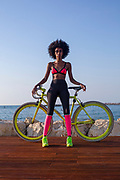 Young athletic woman in sports clothes with her road bicycle near the sea