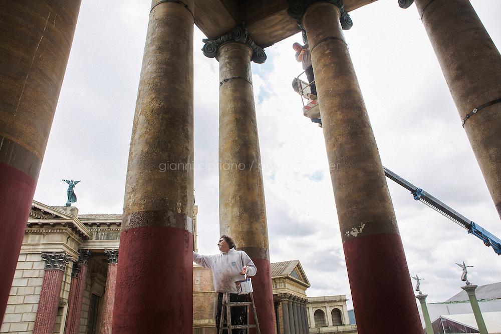 """ROME, ITALY - 30 MARCH 2015: Maintenance workers employed at Cinecittà Studios paint a Roman temple of the set of """"Rome"""", the British-American-Italian broadcasted between 2005 and 2007 on HBO, BBC Two and RaiDue, here in Cinecittà, Rome, Italy, on March 30th 2015.<br /> <br /> Italy instated a special 25% tax credit for film productions in 2010. The industry then lobbied to remove the credit's cap, and last July, Italy lifted its tax credit limit from €5 million per movie to €10 million per company per year. <br />  <br /> Cinecittà, a large film studio in Rome, is considered the hub of Italian cinema. The studios were founded in 1937 by Benito Mussolini as part of a scheme to revive the Italian film industry. In the 1950s, the number of international productions being made here led to Rome being dubbed as the """"Hollywood on the Tiber"""". In the 1950s, Cinecittà was the filming location for several large American film productions like Ben-Hur, and then became the studio most closely associated with Federico Fellini.<br /> After a period of near-bankruptcy, the Italian Government privatized Cinecittà in 1997, selling an 80% stake.<br /> <br /> Currently Ben-Hur and Zoolander 2 are booked into Cinecittà Studios."""