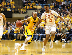 Jan 20, 2018; Morgantown, WV, USA; West Virginia Mountaineers guard Jevon Carter (2) drives towards the basket while guarded by Texas Longhorns guard Jase Febres (13) during the second half at WVU Coliseum. Mandatory Credit: Ben Queen-USA TODAY Sports