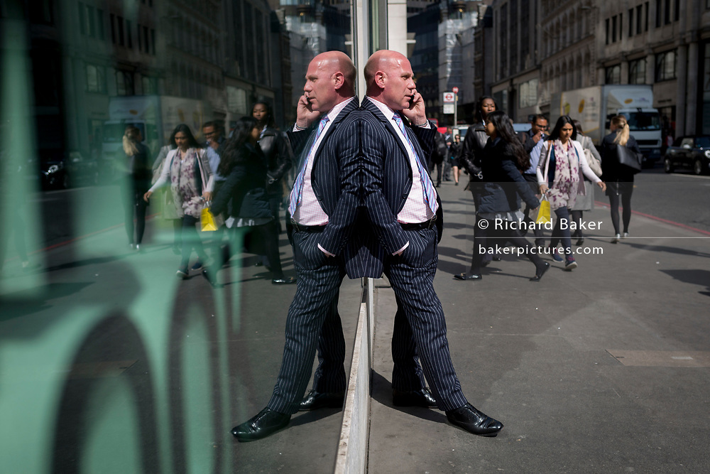A symmetrical gentleman wearing a pinstripe suit talks on his phone, reflected in plate glass in the City of London, the capital's financial district also known as the Square Mile, on 6th April 2017, in London, England.