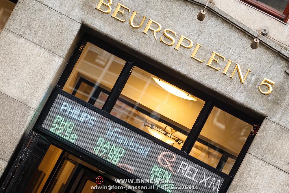 NLD/Amsterdam/20160121 - Winkels in het Amsterdamse straatbeeld, gebouw van Beursplein 5 Amsterdam met de koersen van Philips en Randstad, Nationalde Nederlanden op de gevel
