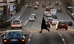 A pedestrian makes a risky crossing of the busy  Rue de la Loi in the European Quarter of Brussels.