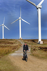 Cyclist cycling past windfarm near Halifax West Yorkshire UK