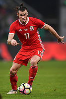 """Gareth Bale of Wales national football team kicks the ball to make a pass against Uruguay national football team in their final match during the 2018 Gree China Cup International Football Championship in Nanning city, south China's Guangxi Zhuang Autonomous Region, 26 March 2018.<br /> <br /> Edinson Cavani's goal in the second half helped Uruguay beat Wales to claim the title of the second edition of China Cup International Football Championship here on Monday (26 March 2018). """"It was a tough match. I'm very satisfied with the result and I think that we can even get better if we didn't suffer from jet lag or injuries. I think the result was very satisfactory,"""" said Uruguay coach Oscar Tabarez. Wales were buoyed by a 6-0 victory over China while Uruguay were fresh from a 2-0 win over the Czech Republic. Uruguay almost took a dream start just 3 minutes into the game as Luis Suarez's shot on Nahitan Nandez cross smacked the upright. Uruguay were dealt a blow on 8 minutes when Jose Gimenez was injured in a challenge and was replaced by Sebastian Coates. Inter Milan's midfielder Matias Vecino of Uruguay also fired at the edge of box from a looped pass but only saw his attempt whistle past the post. Suarez squandered a golden opportunity on 32 minutes when Ashley Williams's wayward backpass sent him clear, but the Barca hitman rattled the woodwork again with goalkeeper Wayne Hennessey well beaten."""