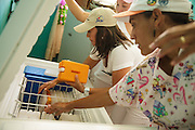 Health workers unpack vaccines from cold boxes as they arrive back at the health center after carrying out house-to-house vaccination in San Esteban, Honduras on Thursday April 25, 2013.
