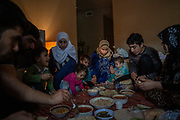 The Alsaloum family eats dinner together on the floor of their temporary apartment shortly after getting settled, in Tampa, Florida, U.S. The space served as a temporary home for the Alsaloum family and got them out of the Days Inn, until the resettlement agency could find a more suitable longterm living situation.
