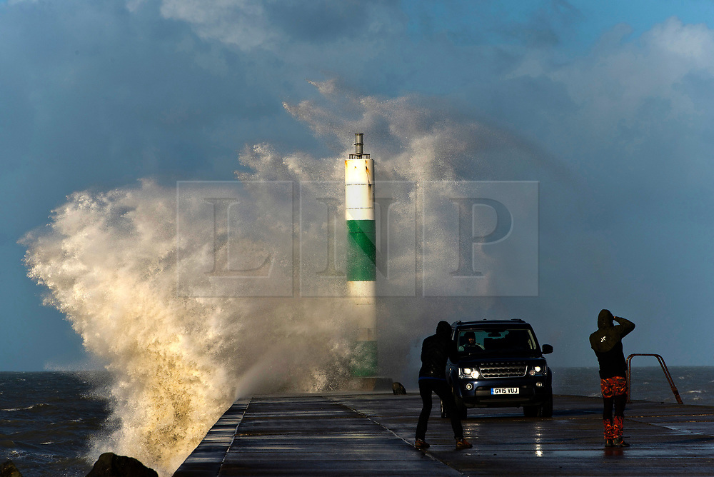 © Licensed to London News Pictures. 15/11/2020. Aberystwyth, Ceredigion, UK. People photograph a 4WD vehicle on the harbour wall as gale force winds and massive waves batters the Welsh seaside resort of Aberystwyth in Ceredigion, UK. Photo credit: Graham M. Lawrence/LNP