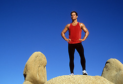 athletic man standing on a rock formation against a blue sky