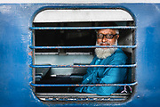 A passenger looks through the open window of a railway carriage before his train departs.