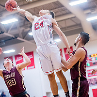 Grants Pirate Gregory Harris (24) reaches long for a rebound above the Belen Eagles at Grants High School Tuesday.