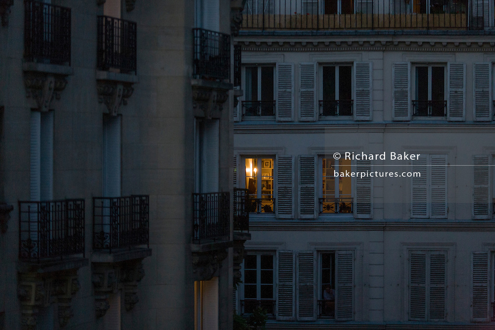 Evening light from apartment rooms glowing on the rue Navarin, 9th Arrondissement, Paris, France.