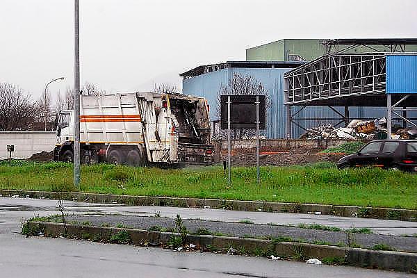 Italie, Aversa, 6-3-2008..Afvalbergen in de straten van Napels en omgeving. De stad weet met zijn afval geen raad meer en in het hele gebied liggen illegale hopen afval. Een nieuwe vuilverbrandingsoven is pas in 2009 bedrijfsklaar. Tot die tijd heeft de maffia, camorra grote invloed op de afvalverwerking van deze stad...Industrieel afval en huishoudelijk afval veroorzaken grote water en bodemvervuiling, terwijl de streek een belangrijk tuinbouwgebied is. Op de foto rijdt een vrachtwagen met huisvuil naat een CDR, een fabriek waar het afval geperst en opgeslagen wordt tot het verwerkt kan worden. Deze fabrieken zijn vol en liggen daarom vaak stil...Foto: Flip Franssen
