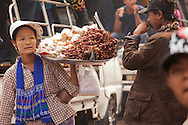 Mandalay, Myanmar- April 14, 2013: Food vendors were popular during Myanmar's Thingyan Water Festival. Thingyan is held in April, one of the hottest months of the year in Myanmar. The water festival marks the country's New Year celebration and the festival includes lots of drinking, singing, dancing and theater. Wherever you are you are likely to get doused with water as the Burmese see this as a cleansing of the previous year's sins and bad luck and a blessing for good luck and prosperity in the year ahead. In the major cities of Mandalay and Yangon, large platforms are erected along major roadways and are equipped with high powered water hoses. The platforms, sponsored by large corporate donors, also have dance stages and play the latest pop and hip hop music. Thousands of residents pour into the streets by foot, motorbike and flatbed truck to get hosed under the platforms while they drink and dance. Many of the young celebrants wear their best clubbing clothes. And many of the party goers are men, having left their wives and girlfriends at home.