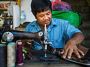 "06 NOVEMBER 2015 - YANGON, MYANMAR: A man repairs luggage at his street stall with a treadle powered sewing machine. Some economists think Myanmar's informal economy is larger than the formal economy. Many people are self employed in cash only businesses like street food, occasional labor and day work, selling betel, or working out of portable street stalls, doing things like luggage repair. Despite reforms in Myanmar and the expansion of the economy, most people live on the informal economy. During a press conference this week, Burmese opposition leader Aung San Suu Kyi said, ""a great majority of our people remain as poor as ever.""  PHOTO BY JACK KURTZ"