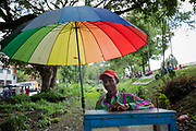 A market street vendor selling popcorn from a mobile stall beneath a colourful, rainbow umbrella, Durbar Square, Bhaktapur, Nepal