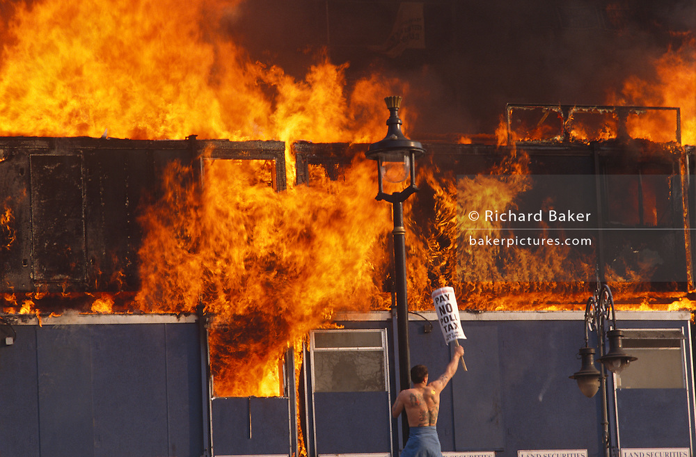 Several metres above the ground, a lone protester hangs on to a street light pole in London's Trafalgar Square at the height of the famous Poll Tax Riot on 31st March 1990 as flames erupt from a building site on The Strand. Angry crowds, demonstrating against Margaret Thatcher's local authority tax, stormed the Whitehall area and then London's West End, setting fire to a construction site and cars, looting stores up Charing Cross Road and St Martin's Lane. The anti-poll tax rally in central London erupted into the worst riots seen in the city for a century. Forty-five police officers were among the 113 people injured as well as 20 police horses. 340 people were arrested.
