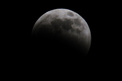 January 21, 2019 - Lanham, MD, U.S - The so-called super wolf moon seen partially within Earth's umbra as the lunar eclipse heads towards totality.  This full moon is referred to as a ''supermoon'' due to its larger apparent size as a result of it taking place near the moon's closest position to Earth, known as its perigee.  It is referred to as a ''wolf'' moon because it is the first full moon in January. (Credit Image: © Evan Golub/ZUMA Wire)