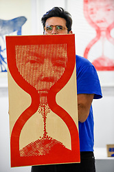 © Licensed to London News Pictures. 05/10/2019. LONDON, UK. Artist Savvas Verdis holds up one of his giant rubber stamps depicting Donald Trump, US President, within an hourglass at The Other Art Fair, presented by Saatchi Art.  120 international, independent artists are displaying their works to be sold direct to buyers.  The fair is taking place at Victoria House in Bloomsbury until 6 October 2019.  Photo credit: Stephen Chung/LNP
