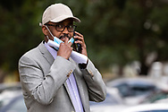 A local community representative is seen talking on his phone in the grounds of 120 Racecourse Road  amid a full and total lockdown of 9 housing commission high rise towers in North Melbourne and Flemington during COVID-19 on 5 July, 2020 in Melbourne, Australia. After 108 new cases where uncovered overnight, the Premier Daniel Andrews announced on July 4 that effective at midnight last night, two more suburbs have been added to the suburb by suburb lockdown being Flemington and North Melbourne. Further to that, nine high rise public housing buildings in these suburbs have been placed under hard lockdown for a minimum of five days, effective immediately.  Residents in these towers will not be allowed to leave their units for any reason. Police will be stationed at every entry and exit point, every level, and they will also surround these locations preventing any movement in, or out. There is a total of 1354 units and over 3000 residents living in these buildings including the states most vulnerable people. These new restrictions will remain in place for fourteen days with fears of further lockdowns to come. The Government have stressed that if Victorians do not follow the basic COVIDSafe rules, the whole state will go back in to lockdown. (Image by Dave Hewison/ Speed Media)