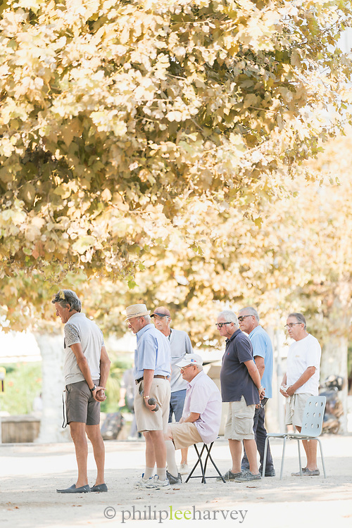 Group of elderly men playing Petanque game on sunny day in park, Cannes, France
