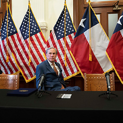 Texas Gov. Greg Abbott eyes the press before signing two bills strengthening the Texas power grid and infrastructure that were emergency items on his legislative agenda. The bills were in response to February's winter storm that nearly knocked out the Texas power grid.  At left is Sen. Kelly Hancock, R-North Richland Hills.